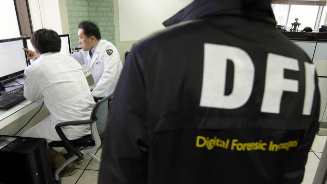 """FILE - In this March 21, 2013 file photo, South Korean computer researchers, left, check the computer servers of Korean Broadcasting System (KBS) as a South Korean police officer from Digital Forensic Investigation watches at the Cyber Terror Response Center at the National Police Agency in Seoul, South Korea. Investigators have yet to pinpoint the culprit behind a synchronized cyberattack in South Korea last week. But in Seoul, the focus remains fixed on North Korea, where South Korean security experts say Pyongyang has been training a team of computer-savvy """"cyber warriors"""" as cyberspace becomes fertile battlegrounds in the standoff between the two Koreas.  (AP Photo/Lee Jin-man, File)"""