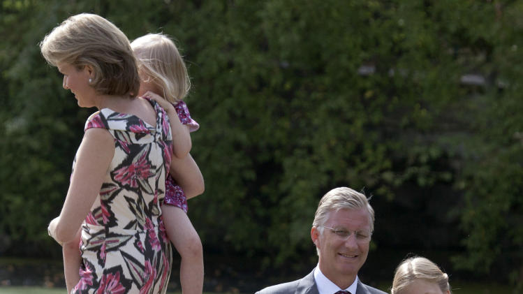 File - In this  Sunday, Sept. 2, 2012 file photo Belgium's Crown Prince Philippe, second from right, sits with his daughter Princess Elisabeth as Princess Mathilde, left, walks with her daughter Princess Eleonore in the grounds of the Royal Palace in Laeken, Belgium. Albert II's kingdom is increasingly threatened by royal-bashing separatists seeking the breakup of Belgium. Now, a book dipping deep into the privacy of kings and princes is adding insult to injury. With its back against the wall, the royal palace sought to strike back in the week of Oct. 29, 2012, seeking action against the journalist who published the book ''Royal Questions'' which is sometimes as rich on dangerous liaisons as it is on the use of anonymous sources. (AP Photo/Virginia Mayo, File)