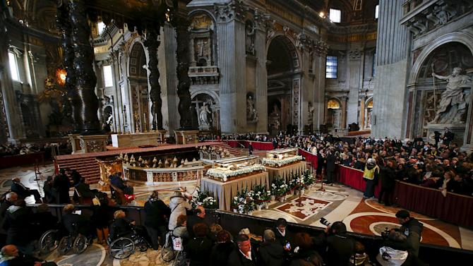 Faithful pray in front of the crystal coffins containing the exhumed bodies of the mystic saint Padre Pio and saint Leopold Mandic displayed in Saint Peter's Basilica during a Jubilee day for the mystic saint Padre Pio at the Vatican