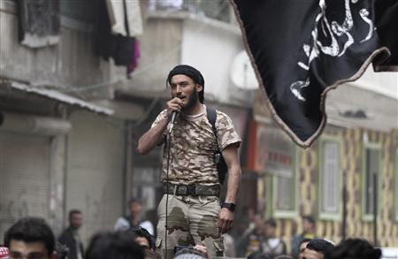 A member of the Free Syrian Army speaks into a microphone during a protest against Syria's President Bashar al-Assad in Bustan al-Qasr district in Aleppo March 22, 2013. REUTERS/Giath Taha