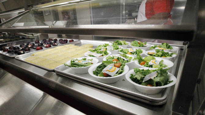 FILE - In this Sept. 12, 2012 file photo, side salads, apple sauce and plums  await the students of Eastside Elementary School in Clinton, Miss. The government for the first time is proposing broad new standards to make school snacks healthier, a move that would ban the sale of almost all candy, high-calorie sports drinks and greasy foods on campus.  (AP Photo/Rogelio V. Solis, File)