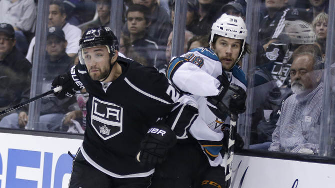 Los Angeles Kings' Alec Martinez, left, keeps San Jose Sharks' Bracken Kearns against the boards during the first period in Game 1 of a second-round NHL hockey Stanley Cup playoff series in Los Angeles, Tuesday, May 14, 2013. (AP Photo/Chris Carlson)