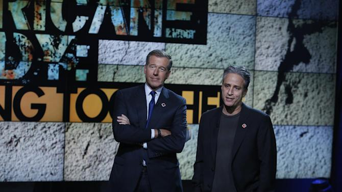 """In this photo provided by NBC, Brian Williams, left, and Jon Stewart perform during """"Hurricane Sandy: Coming Together"""" Friday, Nov. 2, 2012, in New York. Hosted by Matt Lauer, the event is heavy on stars identified with New Jersey and the New York metropolitan area, which took the brunt of this week's deadly storm. (AP Photo/NBC, Heidi Gutman)"""
