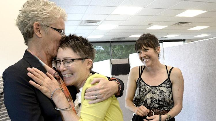 Julie Hoehing, left, and Nancy Cooley, middle, hug and kiss after they were married, while daughter Lia Cooley watches at the Boulder County Clerk and Recorder's Office in Boulder, Colo., Tuesday, July 1, 2014. Although Colorado's constitution bans same-sex marriage, a ruling from the 10th U.S. Circuit Court of Appeals in Denver last week regarding a Utah case said states cannot prevent people from marrying based on their gender. That motivated Boulder County Clerk Hillary Hall to begin issuing marriage licenses, even though the 10th Circuit put its ruling on hold pending an appeal. (AP Photo/The Daily Camera, Mark Leffingwell)