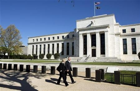 Pedestrians walk past the Federal Reserve Building in Washington