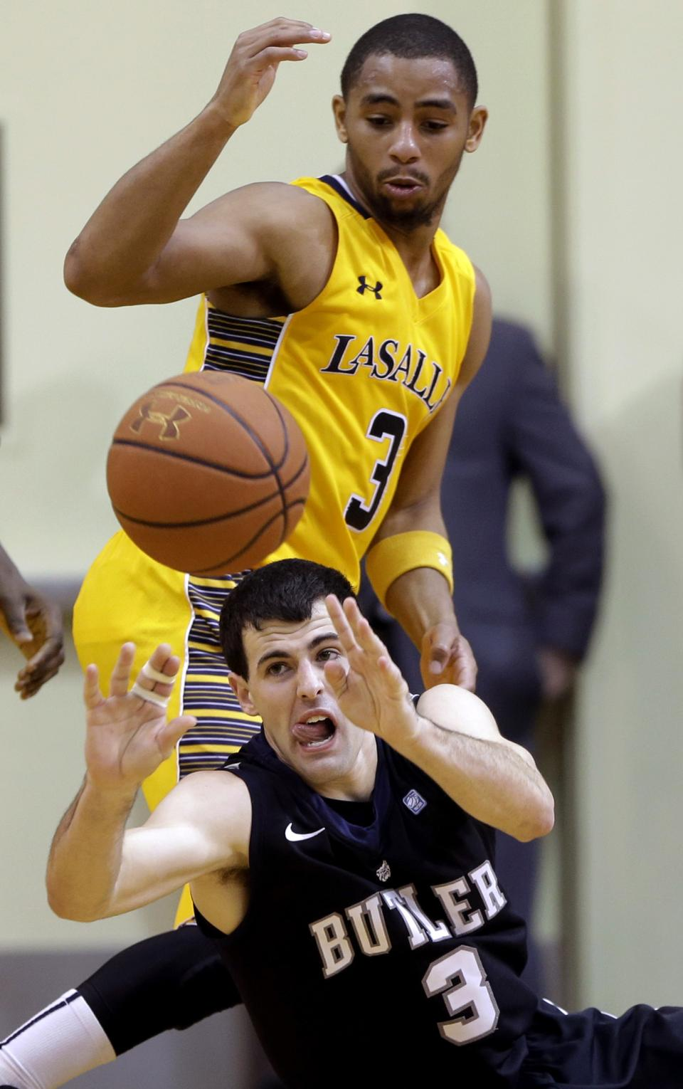 Butler's Alex Barlow, bottom, passes the ball under pressure from La Salle's Tyreek Duren during the second half of an NCAA college basketball game, Wednesday, Jan. 23, 2013, in Philadelphia. La Salle won 54-53. (AP Photo/Matt Slocum)
