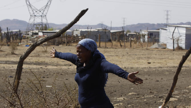 A woman from a group of churchgoers  wails at the site, Sunday Aug. 19, 2012 at the Lonmin platinum mine near Rustenburg, South Africa, during a memorial service for 34 dead striking miners who were shot and killed by police last Thursday.   Miners must return to work Monday or face being fired from the  mine where rivalry between unions has exploded into violence.  (AP Photo/Denis Farrell)