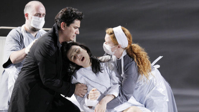 """In this picture taken Wednesday, May 23, 2012, Nenad Marinkovic in the role of Giuseppe, Saimir Pirgu as Alfredo Germont, Irina Lungu as Violetta Valery, and Claire Egan as Nun, from left, perform during a dress rehearsal at the Theater an der Wien in Vienna, Austria, for the opera """"La Traviata"""" by Giuseppe Verdi. (AP Photo/dapd, Lilli Strauss)"""