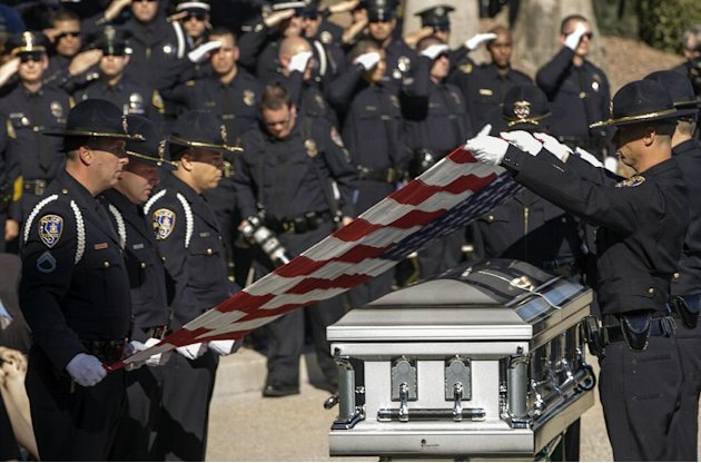 Riverside Police honor guard fold the flag from the coffin of Riverside Police officer Michael Crain, who was allegedly shot to death by accused killer and fired Los Angeles police officer, Christophe