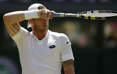Samuel Groth of Australia wipes his forehead during his match against Roger Federer of Switzerland at the Wimbledon Tennis Championships in London