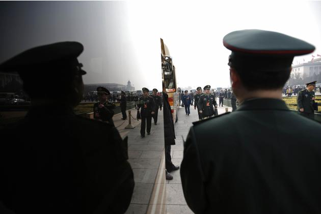 A military member waits for delegates to board, near the Great Hall of the People after a plenary session of NPC in Beijing