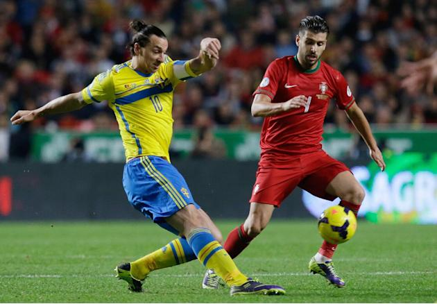 Sweden's Zlatan Ibrahimovic, left, fights for the ball with Portugal's Miguel Veloso during the World Cup qualifying playoff first leg soccer match between Portugal and Sweden Friday, Nov. 15 2013, at