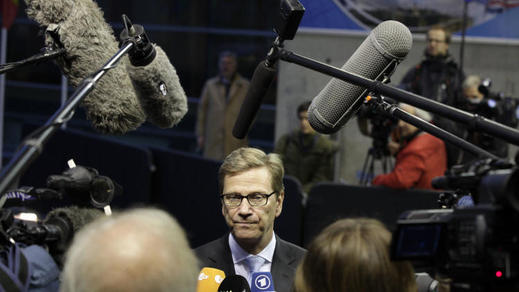 German Foreign Minister Guido Westerwelle, center, speaks with the media as he arrives for a meeting of EU Foreign Ministers in Luxembourg on Monday Oct. 15, 2012. Britain, Germany and France say they expect the European Union to approve even tougher sanctions on Iran to prevent it from developing nuclear weapons. (AP Photo/Virginia Mayo)