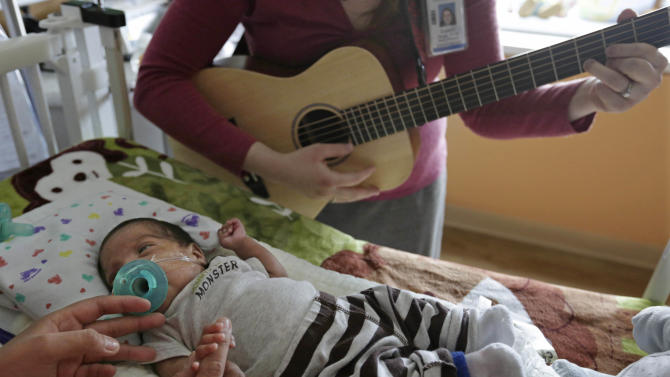 Music therapist Elizabeth Klinger, right, quietly plays guitar and sings for Augustin as he grips the hand of his mother, Lucy Morales, in the newborn intensive care unit at Ann & Robert H. Lurie Children's Hospital in Chicago on Monday, May 6, 2013. Research suggests that music may help those born way too soon adapt to life outside the womb. Recent studies and anecdotal reports suggest the vibrations and soothing rhythms of music, especially performed live in the hospital, might benefit preemies and other sick babies. (AP Photo/M. Spencer Green)