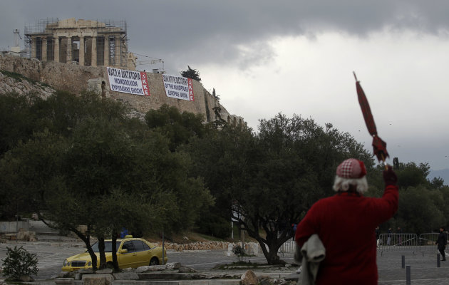 A Pedestrian gestures as banners in Greek and English denouncing EU policies are hung by Greek communist party members under the temple of Parthenon at the Athens' Acropolis hill on Saturday Feb. 11,