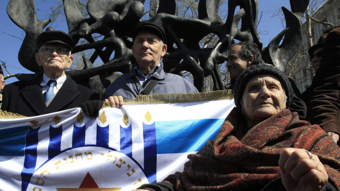 """Survivors of the concentration camps,  from left Moshe Haelion,  Abraham Ashkenazi and Zana Santicario Saatsoglou, hold a banner that reads in Hebrew :""""The organization of death camps survivors from Greece in Israel"""" in the northern port city , of Thessaloniki, Greece, on Saturday, March 16, 2013. Jewish residents in this northern Greek city have gathered to commemorate the 70th anniversary from the first roundup and deportation of Jews to Nazi extermination camps in World War II. By August 1943, 46,091 Jews had been deported to Auschwitz-Birkenau. Of those, 1,950 survived. (AP Photo/Nikolas Giakoumidis)"""