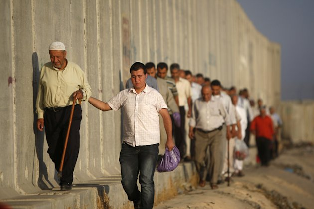 Palestinian men walk towards an Israeli checkpoint on their way to pray at the Al-Aqsa Mosque in Jerusalem, on the last Friday of the Muslim holy month of Ramadan near the West Bank city of Ramallah, Friday, Aug. 17, 2012.(AP Photo/Majdi Mohammed)