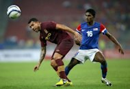 Manchester City's player Carlos Tevez (L) shields the ball from Malaysia's player S. Kunanlan during their football friendly match in Bukit Jalil Stadium, some 20 kilometres south of Kuala Lumpur. Manchester City manager Roberto Mancini expressed confidence his champion squad will be able to retain their Barclays Premier League trophy after beating Malaysia in style