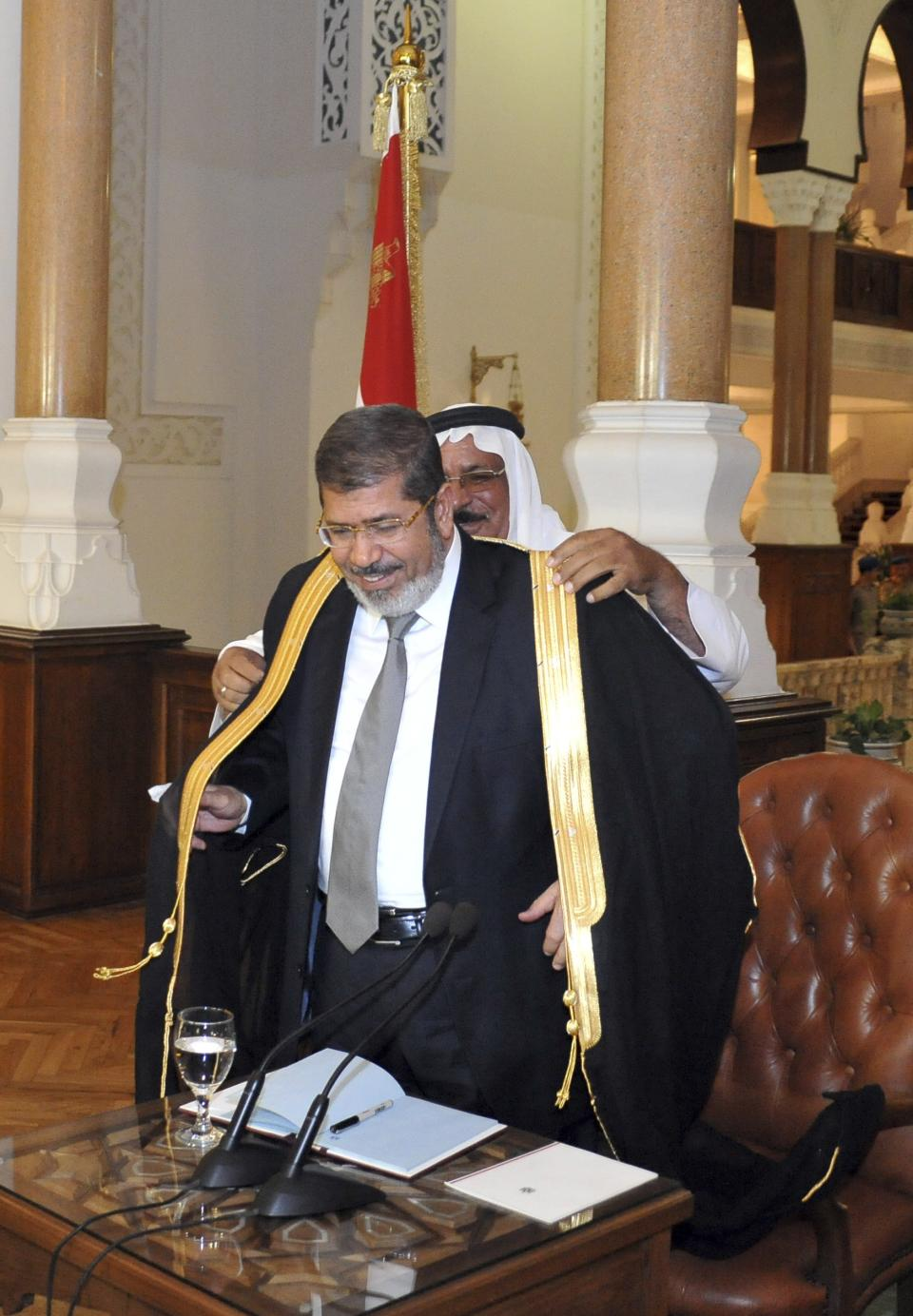 In this photo released by the Egyptian Presidency, President-elect Mohammed Morsi is given a traditional robe during a meeting with political party representatives in Cairo, Egypt, Thursday, June 28, 2012. (AP Photo/Egyptian Presidency)