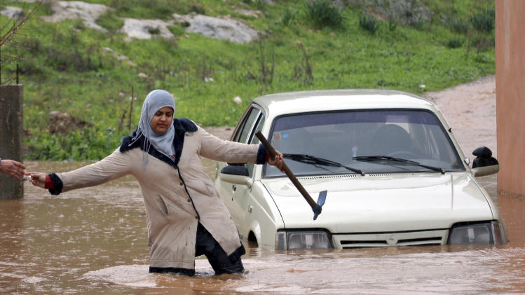 A Palestinian woman passes keys to a person on the other side of a flooded road in the West Bank of Jenin, Tuesday, Jan. 8, 2013. Stormy weather, including high winds and heavy rainfall, lashed Israel and the Palestinian territories, downing power-lines and trees. (AP Photo/Mohammed Ballas)