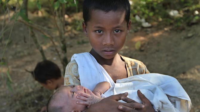 In this photo taken on Nov. 8, 2012, a Rakhine boy carries a baby at a relief camp in Mrauk-U, Rakhine state, western Myanmar. Mrauk-U itself has been spared the bloodshed between the Buddhist Rakhine and the Muslim Rohingya that has scarred other parts of Rakhine state. It is calm, and for foreign tourists, safe. But just 10 kilometers (six miles) to the south, there is a village where civilians were reportedly beheaded in a massacre last month that saw women and children slaughtered, then buried in mass graves. Across western Myanmar's Rakhine state, the United Nations is distributing emergency supplies of food and shelter to terrified villagers who have fled burning homes. A nighttime curfew is in force. (AP Photo/Khin Maung Win)