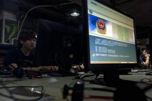 FILE - In this Monday, Aug. 19, 2013 file photo, computer users sit near a display with a message from the Chinese police on the proper use of the internet at an internet cafe in Beijing, China. The Chinese government has declared victory in its recent campaign to clean up what it considers rumors, negativity and unruliness from online discourse, while critics say the moves have suppressed criticism of the government and ruling Communist Party. (AP Photo/Ng Han Guan, File)