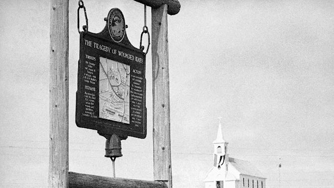 FILE - This undated file photo shows the historical marker commemorating the Wounded Knee Massacre of 1890 on the road near the Sacred Heart Catholic Church in Wounded Knee, S.D.  James Czywczynski  is trying to sell a 40-acre parcel of nearby land he owns, a fraction of the Wounded Knee National Historic landmark, for $3.9 million to the Oglala Sioux Tribe. But leaders on the Pine Ridge Indian Reservation say the asking price for a property appraised at less than $7,000 is just too much. (AP Photo/File)