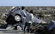 A family looks at a damaged vehicle following a tsunami in the aftermath of a massive 8.9 earthquake in Minamisoma, Fukushima Prefecture on March 12, 2011. Japan on Friday insisted warnings by the World Health Organisation of a rise in the risk of cancer for people in Fukushima were overblown, saying the agency was unnecessarily stoking fears