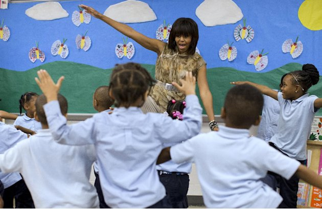 First lady Michelle Obama dances with a pre-Kindergarten class at Savoy Elementary School in Washington, Friday, May 24, 2013. The Savoy School was one of eight schools selected last year for the Turn