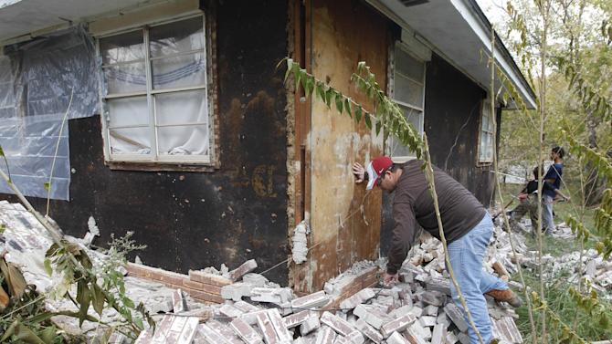 FILE - Chad Devereaux examines bricks that fell from three sides of his in-laws home in Sparks, Okla. on Sunday, Nov. 6, 2011 after two earthquakes hit the area in less than 24 hours. A team of scientists have determined that a 5.6 magnitude quake in Oklahoma in 2011 was caused when oil drilling waste was injected deep underground. The report was released Tuesday, March 26, 2013 by the journal Geology. That makes it the most powerful quake to be blamed on deep injections of wastewater, although not everyone agrees. Oklahoma's state seismologists say the quake was natural. (AP Photo/Sue Ogrocki, File)