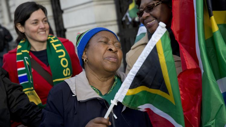 A woman reacts following the death of former South African President Nelson Mandela, at the South African High Commission in London