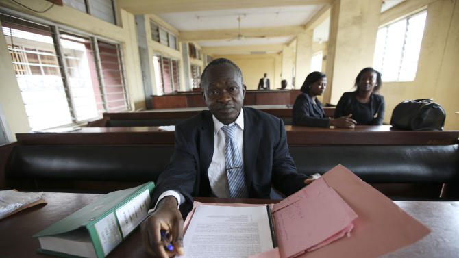 Leonard Dibia,  a lawyer  representing  victims of crash look through court documents during a ruling at the Magistrate court in Lagos, Nigeria,  Wednesday, April. 25, 2012,The failures of Africa's most populous nation seemed to explode into a fiery multiple car and truck crash in Nigeria that killed at least 18 people in 2010, according to a coroner's ruling issued Wednesday. Police set up an illegal checkpoint August 2010 along a major expressway in Lagos, using tires to funnel traffic down to one lane as officers demanded bribes from motorists, witnesses said. The driver of a speeding truck carrying sugar for the nation's largest industrial company tried to stop, but the vehicle's bad brakes failed and the truck slammed into waiting traffic, witnesses and officials said. Those details, long denied by authorities, came out Wednesday when a coroner investigating the deaths ruled against Nigeria's federal police and the Dangote Group, owned by billionaire Aliko Dangote. (AP Photos/Sunday Alamba)