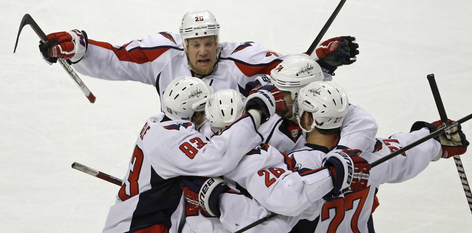 Washington Capitals' Jason Chimera, top, joins teammates to celebrate a goal by Matt Hendricks against the Boston Bruins during the first period of Game 7 of an NHL hockey Stanley Cup first-round playoff series, in Boston on Wednesday, April 25, 2012. AP Photo/Charles Krupa)