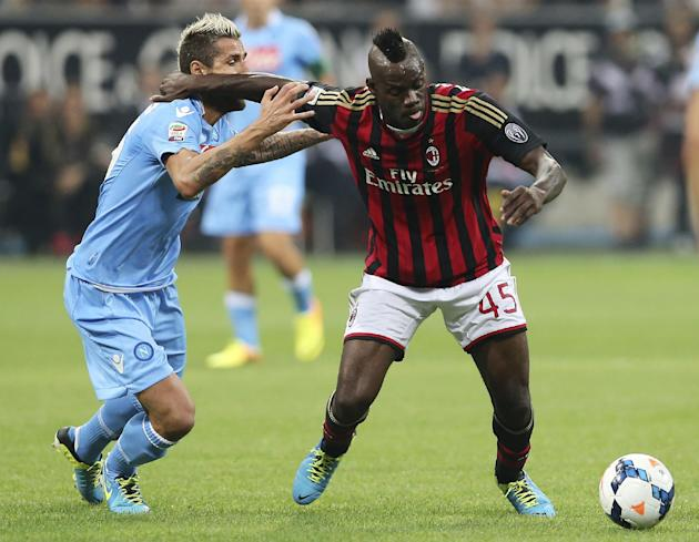 AC Milan forward Mario Balotelli, right, holds back Napoli midfielder Valon Behrami, of Switzerland, during the Serie A soccer match between AC Milan and Napoli at the San Siro stadium in Milan, Italy