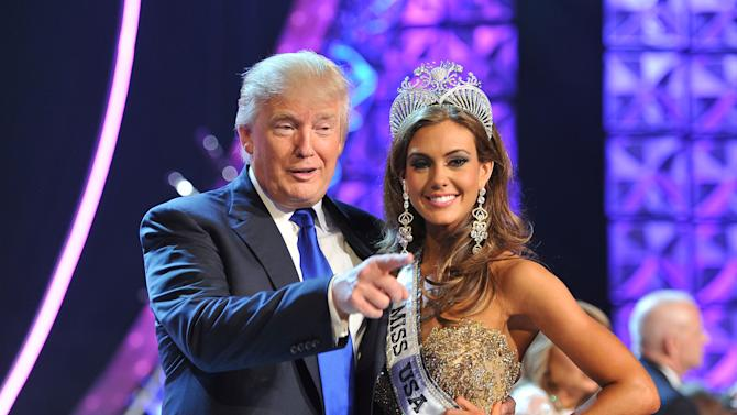 FILE - In this June 16, 2013, file photo, Donald Trump, left, and Miss Connecticut USA Erin Brady pose onstage after Brady won the 2013 Miss USA pageant in Las Vegas. The Reelz channel said Thursday, July 2, 2015, it will carry Trump's Miss USA pageant that was dropped by NBC after Trump made critical comments about immigrants from Mexico. (AP Photo/Jeff Bottari, File)
