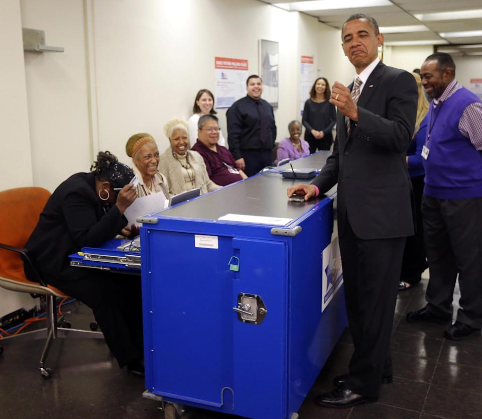 President Barack Obama playfully jokes around with the way election official Marie Holmes, left, looked over his drivers license during early voting, in the 2012 election at the Martin Luther King Community Center, Thursday, Oct. 25, 2012, in Chicago. (AP Photo/Pablo Martinez Monsivais)