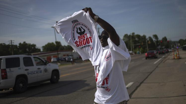 A man sells T-shirts along the roadside in Ferguson, Missouri