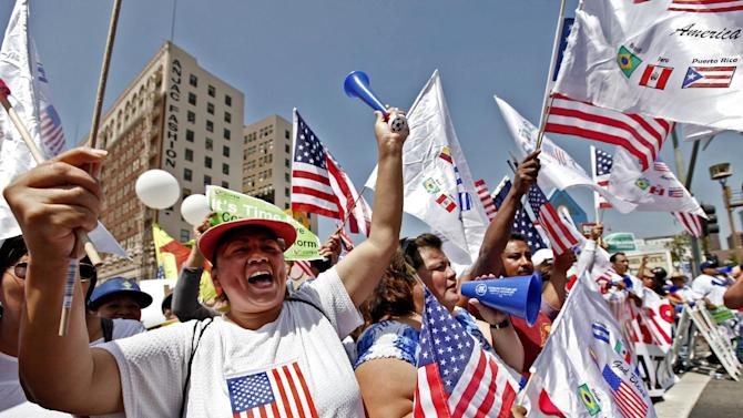 Alma Banuelos, left, with Emilia Hernandez  shout slogans during a rally in downtown Los Angeles Wednesday, May 1, 2013. In celebration of May Day thousands have gathered for an immigration reform rally in downtown Los Angeles. (AP Photo/Nick Ut)