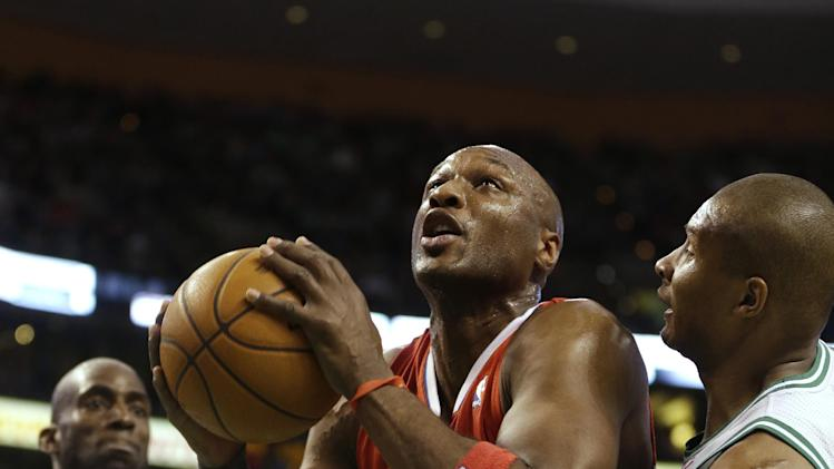 Los Angeles Clippers forward Lamar Odom, center, drives toward the basket while under pressure from Boston Celtics forward Kevin Garnett (5), left, and guard Leandro Barbosa, right, in the second quarter of an NBA basketball game at the TD Garden in Boston, Sunday, Feb. 3, 2013. (AP Photo/Steven Senne)