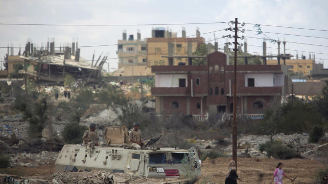 Egyptian army forces patrol on the Egyptian side of the border town of Rafah after the army demolished houses as seen from the Palestinian side of Rafah in the southern Gaza Strip on Thursday, Oct. 30, 2014. With dynamite and bulldozers, Egypt's army demolished homes along its border with the Gaza Strip on Thursday, after the military ordered residents out on Wednesday to make way for a planned buffer zone meant to stop militants and smugglers. (AP Photo/Khalil Hamra)
