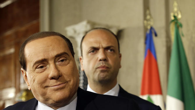 FILE - In this April 23, 2013 file photo, then People of Freedom party leader Silvio Berlusconi, left, is followed by party secretary Angelino Alfano as they meet journalists after talks with Italian President Giorgio Napolitano, in Rome's Quirinale presidential palace during consultations to form a new government. Berlusconi's political heir, Alfano, currently Interior Minister and Deputy Premier, announced Friday Nov. 16, 2013, that he was leaving Berlusconi's party to form a new political group, creating a schism in Italy's center-right that raised fresh questions about the stability of the government. (AP Photo/Gregorio Borgia, files)