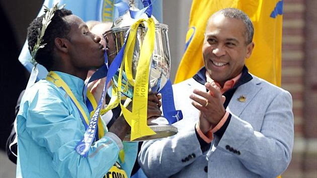 Lelisa Desisa Benti of Ethiopia kisses the Boston Marathon trophy in front of Massachusetts Governor Deval Patrick (Reuters)