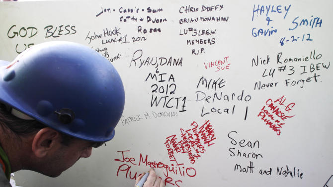"FILE- In this Aug. 2, 2012 file photo, a construction worker signs a ceremonial steel beam at One World Trade Center in New York. The beam was signed by President Barack Obama with the notes: ""We remember,"" ''We rebuild"" and ""We come back stronger!"" during a ceremony at the construction site June 14. The beam, having since adorned with the autographs of workers and police officers at the site, will be sealed into the structure of the tower, which is scheduled for completion in 2014. (AP Photo/Mark Lennihan, File)"