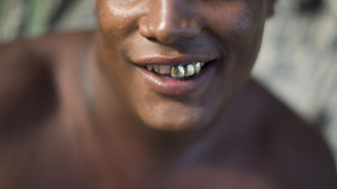 "In this photo taken Dec. 8, 2012, a drug dealer smiles for pictures at a drug selling point in a slum of Rio de Janeiro, Brazil. The South American country began experiencing a public health emergency in recent years as demand for crack boomed and open-air ""cracolandias,"" or crack lands, popped up in the sprawling urban centers of Rio and Sao Paulo, with hundreds of users gathering to smoke the drug. The federal government announced in early 2012 that more than $2 billion would be spent to fight the epidemic, with the money spent to train local health care workers, purchase thousands of hospital and shelter beds for emergency treatment, and create transitional centers for recovering users. (AP Photo/Felipe Dana)"