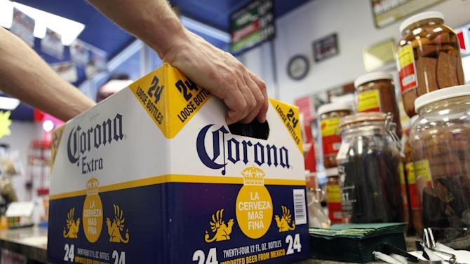 FILE - In this April 1, 2010 file photo, a customer places a case of Corona Extra on the checkout counter for purchase at Susquehanna Beer and Soda in Marysville, Pa. Anheuser-Busch InBev SA agreed Friday, June 29, 2012, to buy the half of Corona maker Grupo Modelo it doesn't already own for $20.1 billion in cash, in a deal that will greatly increase the size and dominance of the world's largest brewer. (AP Photo/Carolyn Kaster, File)