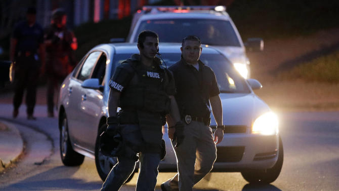 A police officer leaves the scene after an explosion and gunshots were heard near the scene where a man was holding four firefighters hostage Wednesday, April 10, 2013 in Suwanee, Ga. A police spokesman said the suspect was dead and none of the hostage suffered serious injuries.  (AP Photo/John Bazemore)