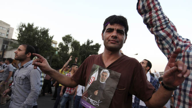 A supporter of Iranian presidential candidate Hasan Rowhani, shown in poster, attends a celebration gathering in Tehran, Iran, Saturday, June 15, 2013. Moderate cleric Hasan Rowhani was declared the winner of Iran's presidential vote on Saturday after gaining support among many reform-minded Iranians looking to claw back a bit of ground after years of crackdowns. (AP Photo/Vahid Salemi)