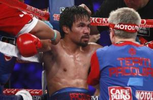 Pacquiao is treated in his corner between rounds of his title fight against undefeated WBO welterweight champion Bradley in Las Vegas