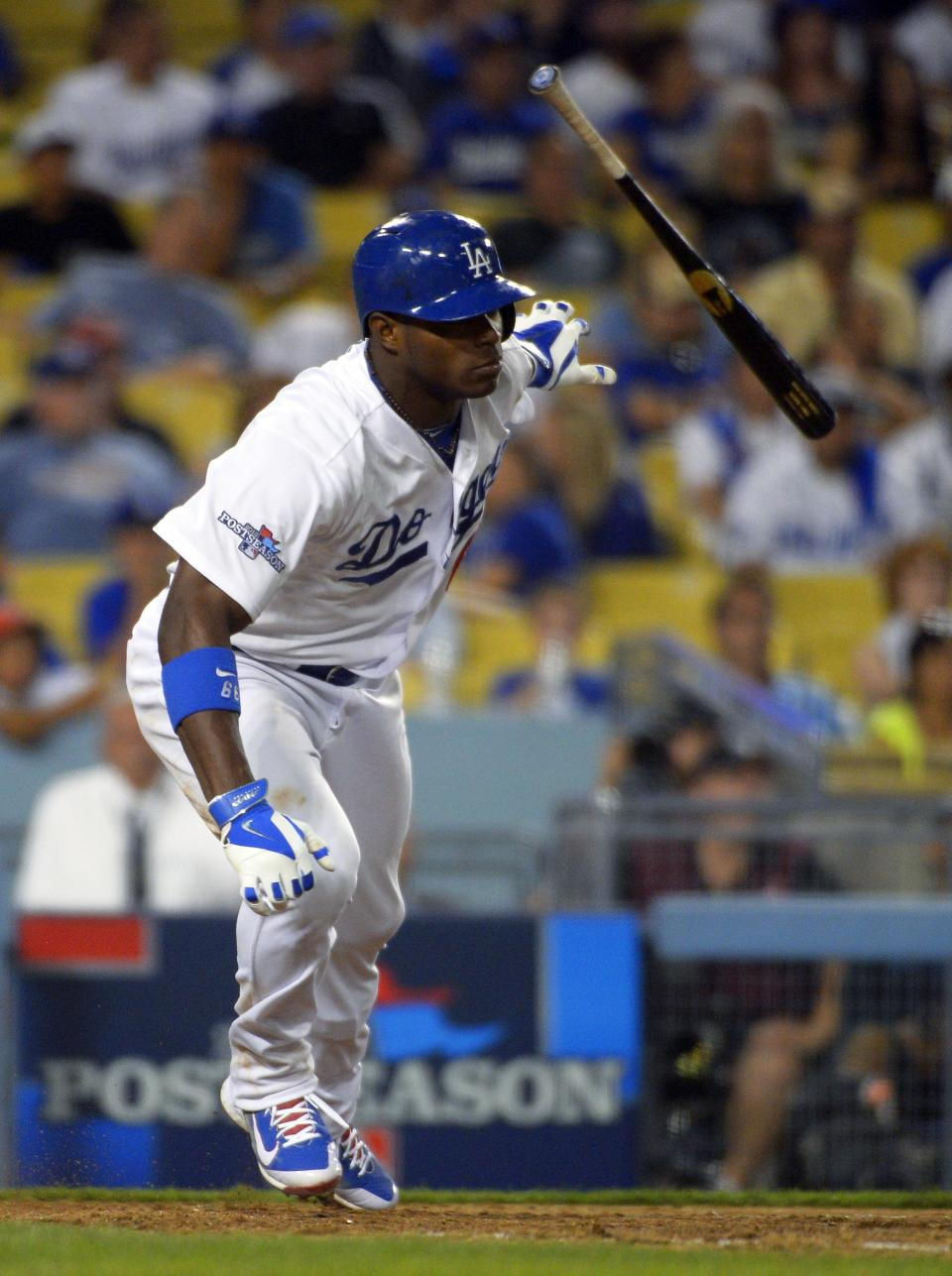 Los Angeles Dodgers' Yasiel Puig tosses his bat after he hit a RBI single against the Atlanta Braves in the eighth inning of Game 3 in the National League division baseball series Sunday, Oct. 6, 2013, in Los Angeles. The Dodgers beat the Braves, 13-6. (AP Photo/Mark J. Terrill)