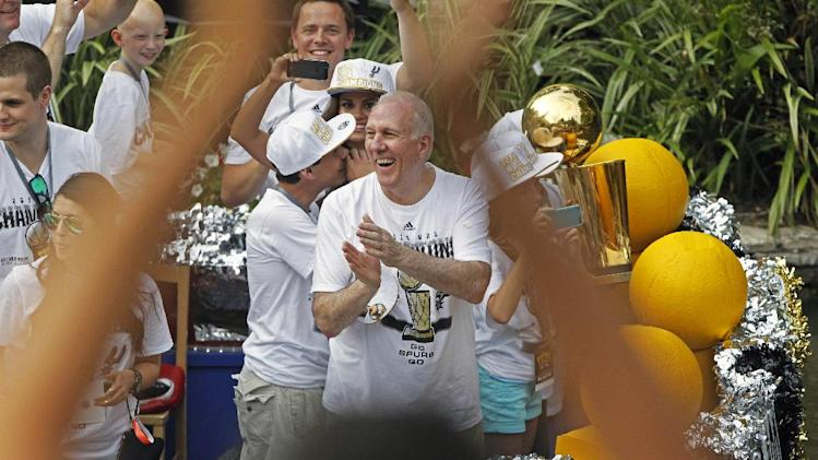 San Antonio Spurs head coach Gregg Popovich, center, claps during the basketball team's parade and celebration of their fifth NBA Championship, Wednesday,  June 18, 2014, in San Antonio. The Spurs defeated the Miami Heat for the title